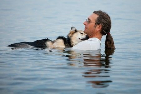 19 year old [Schoep] is being cradled in his father's arms [July 31] in Lake Superior. [Schoep] falls asleep every night when he is carried into the lake. The buoyancy of the water soothes his arthritic bones. Lake Superior is very warm right now, so the temp of the water is perfect.     The Washington Post
