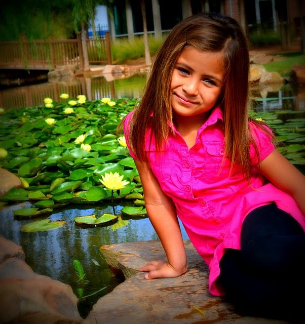 beautiful 5 year old girl with yellow blooming lillies in background