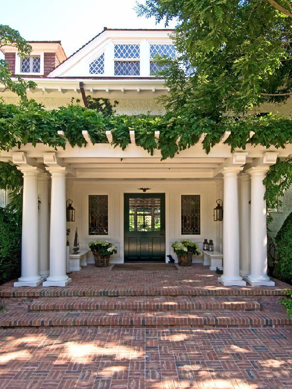 Columns, vine covered arbor, leaded glass windows, brick drive and porch