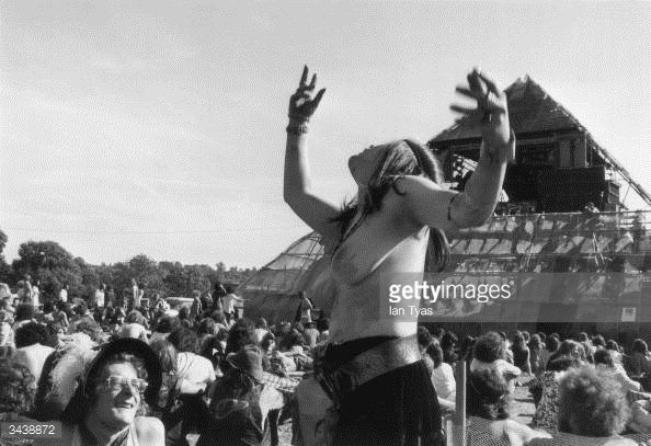 A young woman dances topless in front of the pyramid stage at the second Glastonbury fayre organised by Arabella Churchill and Andrew Kerr at Worthy...