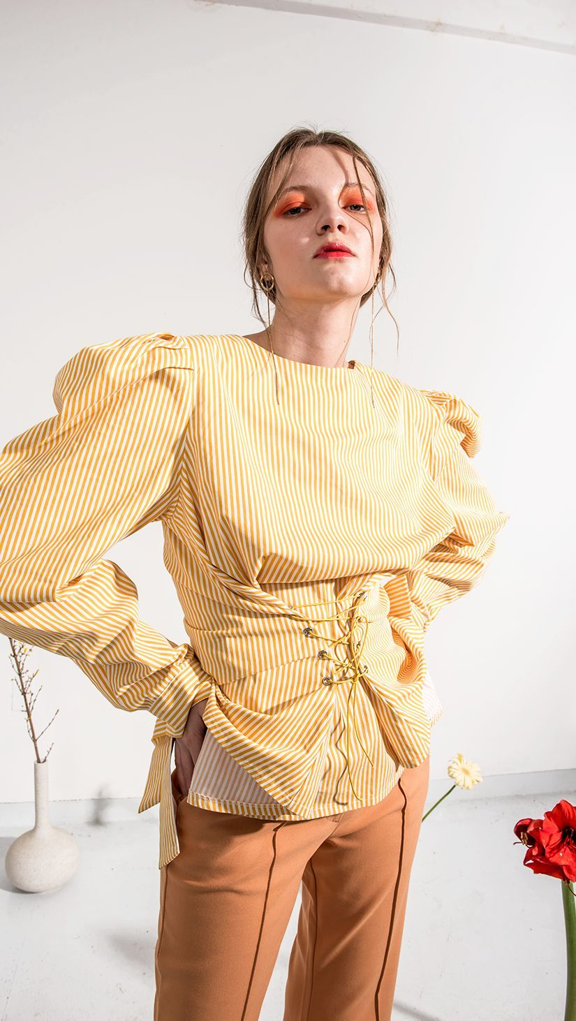 The Claudia corset top in yellow stripes pattern. With puff long sleeves and button down back detailing. Voluminous shape. COMPOSITION AND CARE Hand wash or delicate washing machine cycle Please treat