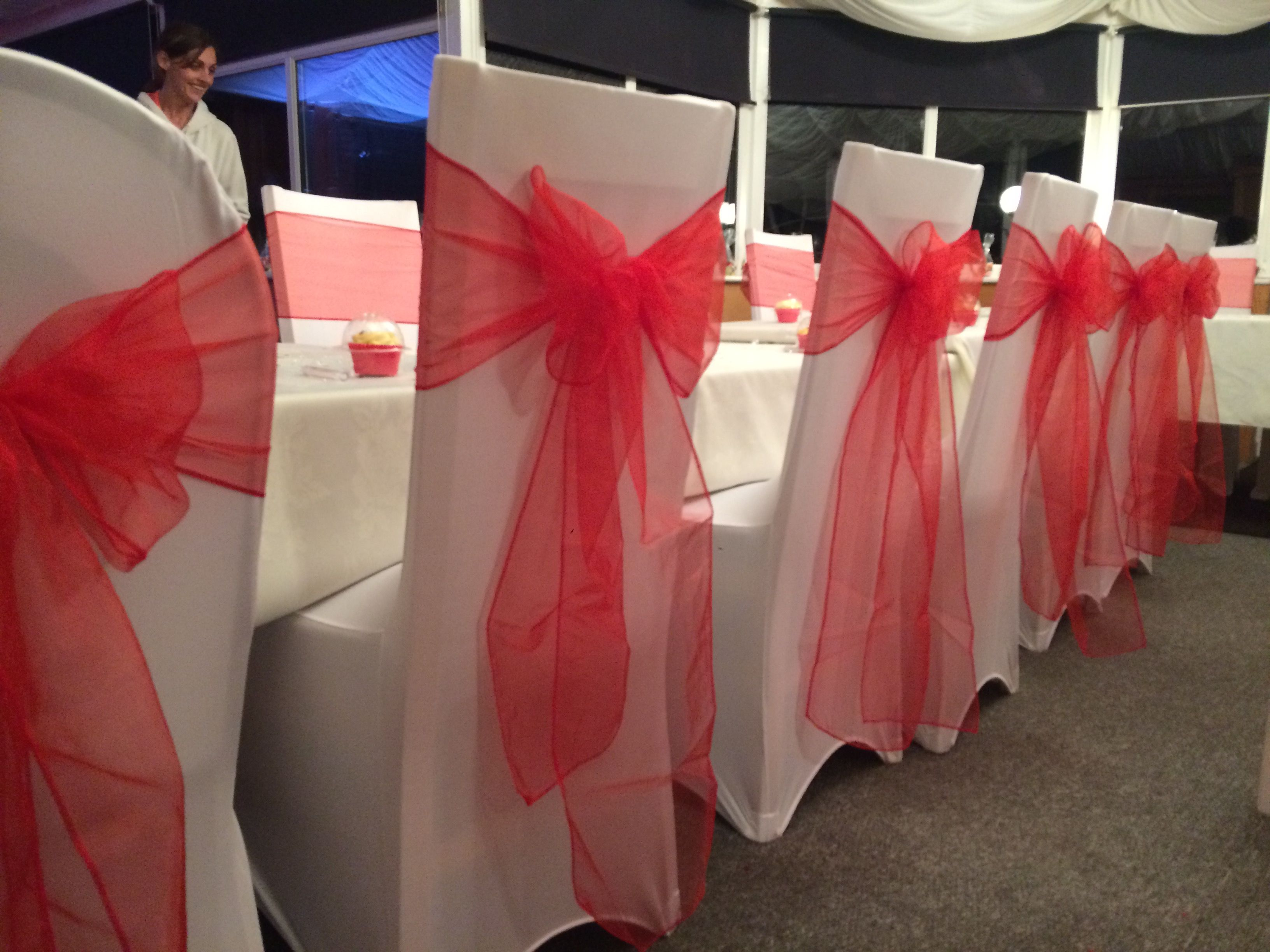 White Chair Covers And Red Organza Sashes At A Wedding Reception In South Wales Dressed By Affinity Event Decorators Wedding Hire Wedding Wedding Party