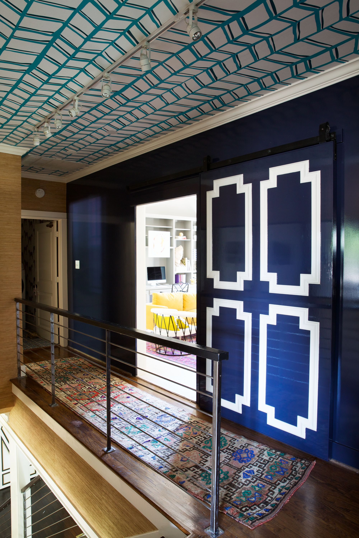 Wallpapered ceiling and custom navy barn doors