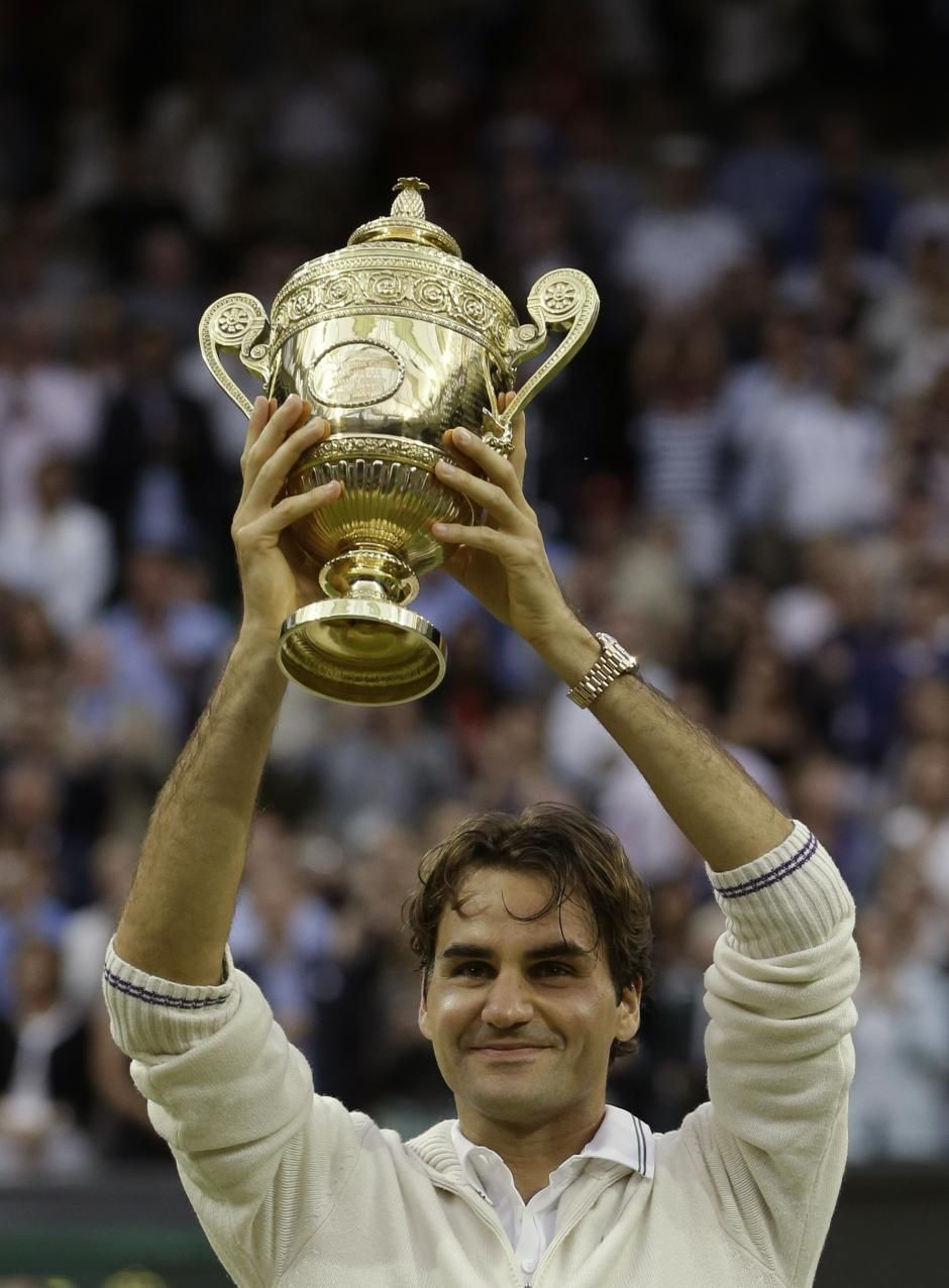 Roger Federer of Switzerland poses with the trophy after winning the men's singles final against Andy Murray of Britain at Wimbledon, England, July 8, 2012.