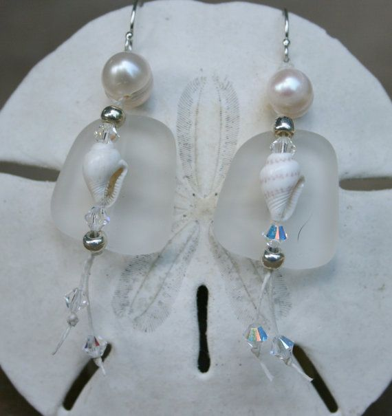 Translucent white seaglass suspended from a white freshwater pearl  accented with nassa shell, seed beads, and Swarovski crystals.