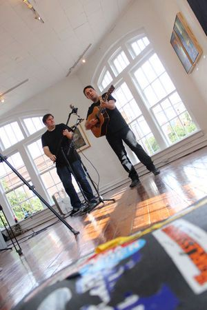 """The twang of a guitar reverberated off walls lined with paintings, around a room crammed with sculptures—a dizzying array of colors jumping off the otherwise white walls. """"Squeaky floor!"""" someone yelled, and everyone froze before moving gingerly in stocking feet to find a seat during the recording. Jeff Austin wiped a streak of sweat from his forehead as he turned from the bay windows overlooking a bustling Churton Street. He strummed again, humming, before launching into his next tune."""