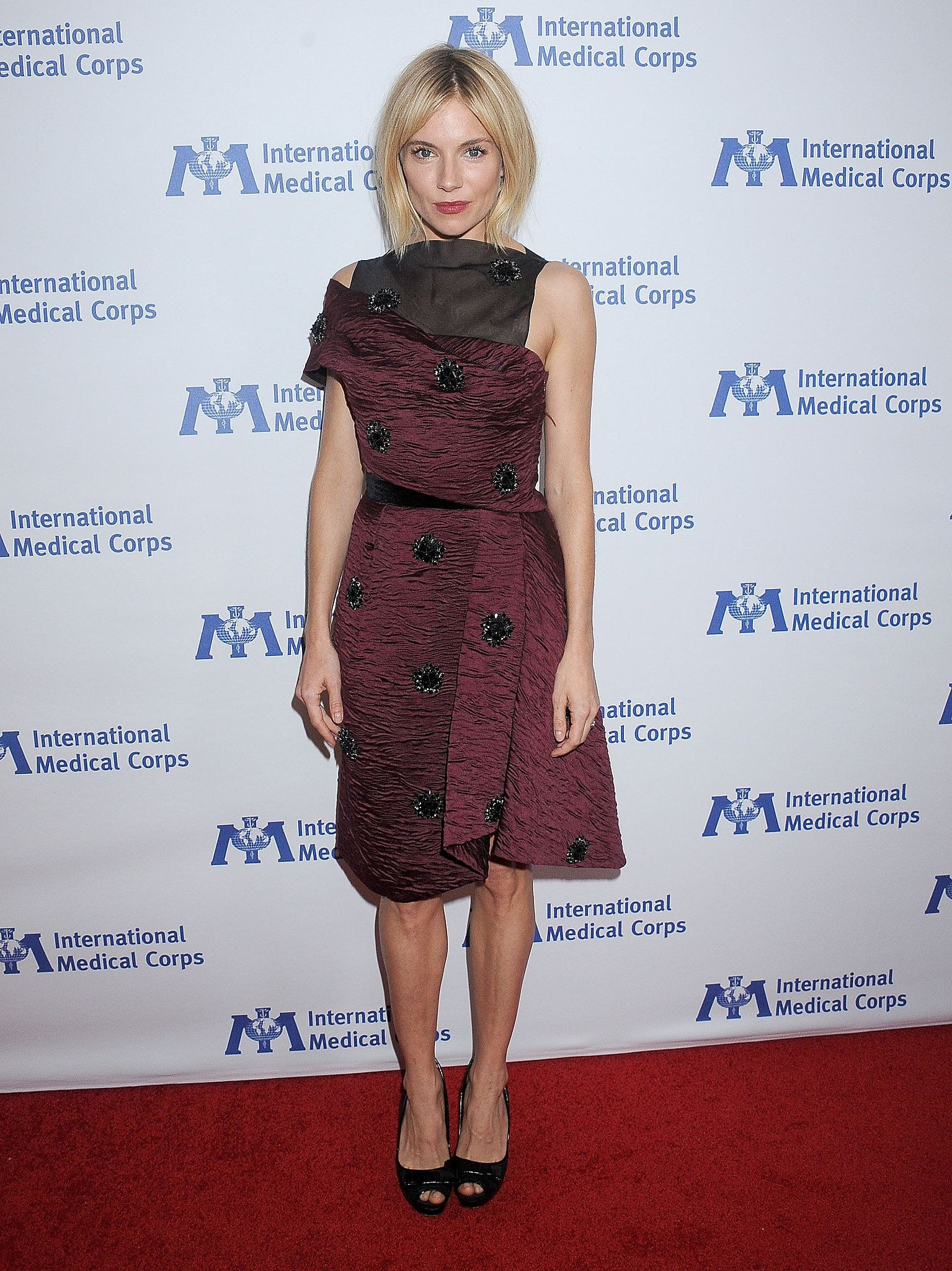 Sienna Miller stepped out in a chic burgundy dress for the International Medical Corps' dinner in Beverly Hills.
