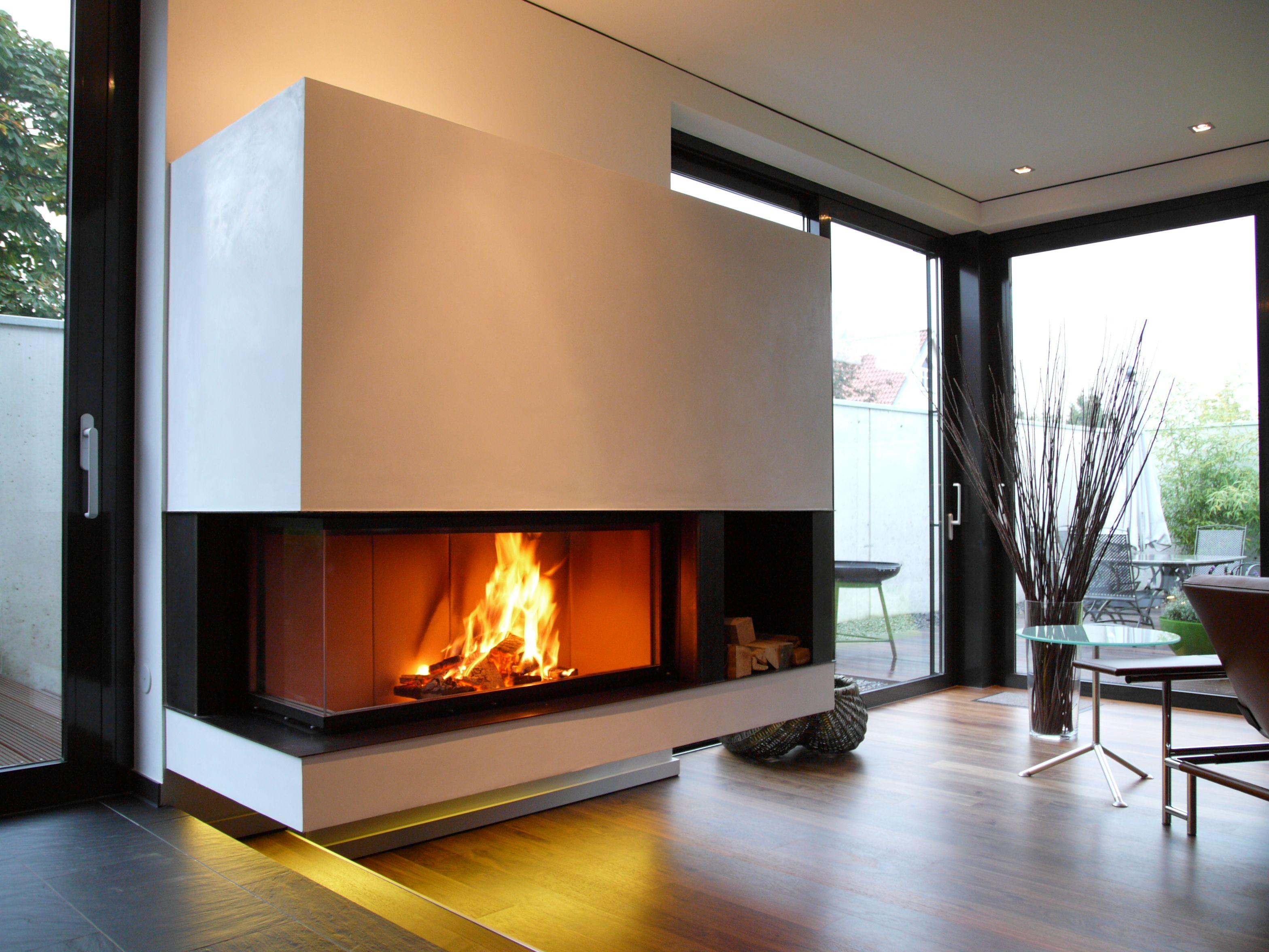 BRUNNER schwebender Eckkamin mit Feuerraumfortführungen und Holzfach. BRUNNER floating fireplace with furnace additions and wood shelf.