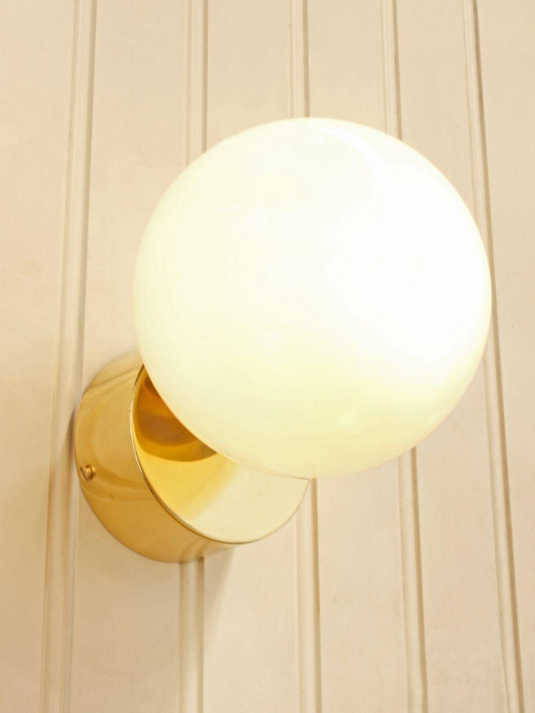 Retro wall light with a polished brass backplate and opal glass
