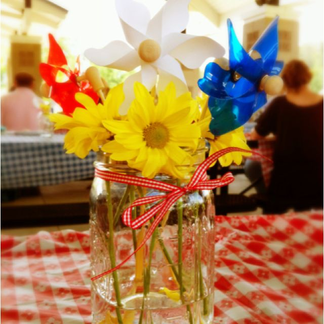 Centerpiece for old-fashioned picnic: Mason jars, yellow daisies, dollar store red, white, and blue pinwheels
