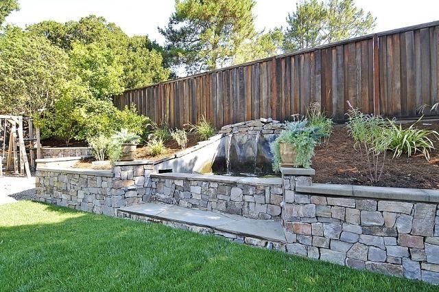 gartenzaun aus holz-stützmauer mit wasser-brunnen-kunstrasen