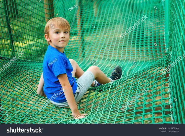 Nette Kletterseil-Hindernisaktivität des kleinen Jungen an