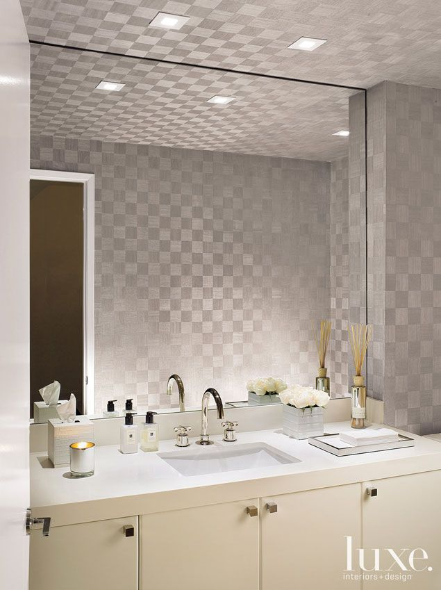 Maya Romanoff wallpaper from Donghia clads the powder room, featuring a  Waterworks sink and faucet.