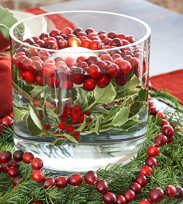 Cranberries floating above holly leaves-and-berries in a water-filled glass bowl encircle a centerpiece candle like a wreath. Evergreen branches and a cranberry garland finish the table decoration.