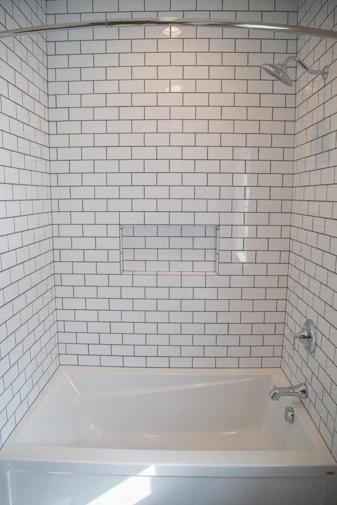 white subway tile shower and niche with