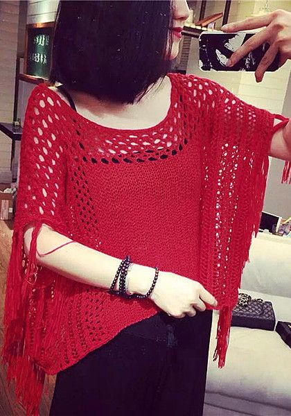 Angled shot of model in red perforated knit top