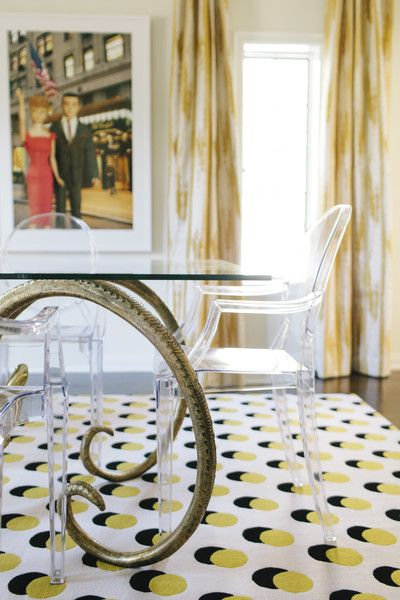 A contemporary dining room with lucite chairs and gold and yellow accents.