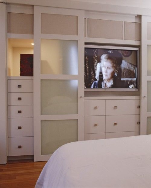 Closet Sliding Doors With Hidden Flat Tv Inside In The Master Bedroom