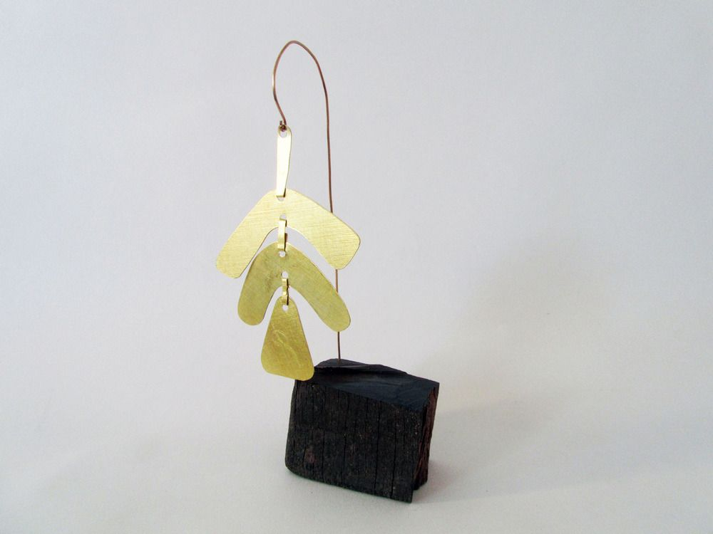 Something for your desk perhaps, a little brass mobile. Hand cut pieces are rolled and patterned then riveted together. A small block of Ekki hardwood serves as a base.