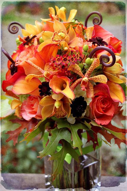A fall bouquet with a variety of orange flowers and oak Fall floral arrangements