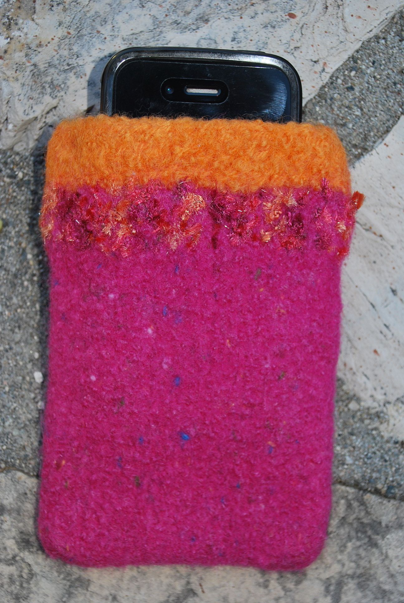 """This phone case is hand-knit and felted from 100% wool yarn. The result is a super sturdy and fun protective pouch. The dimensions are 5 1/2"""" x 3 1/2"""". It fits an iphone/ipod or most other cell phones. Colors are hot pink and light orange with a multicolored novelty yarn accent."""