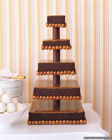 Five tiers of dense chocolaty brownies glazed with caramel and trimmed with candied pecans