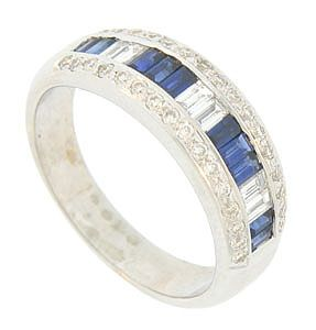 A dazzling band of diamond and sapphire baguettes press into the face of this spectacular 18K white gold wedding band. Additional fine faceted round cut diamonds frost the edges of the antique style wedding ring. This elegant ring measures 7.01 mm in width. Size 8 1/4. We can re-size slightly.