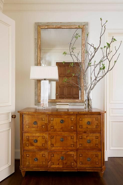 Chic foyer features a gray and gold mirror placed over a 9 drawer ...