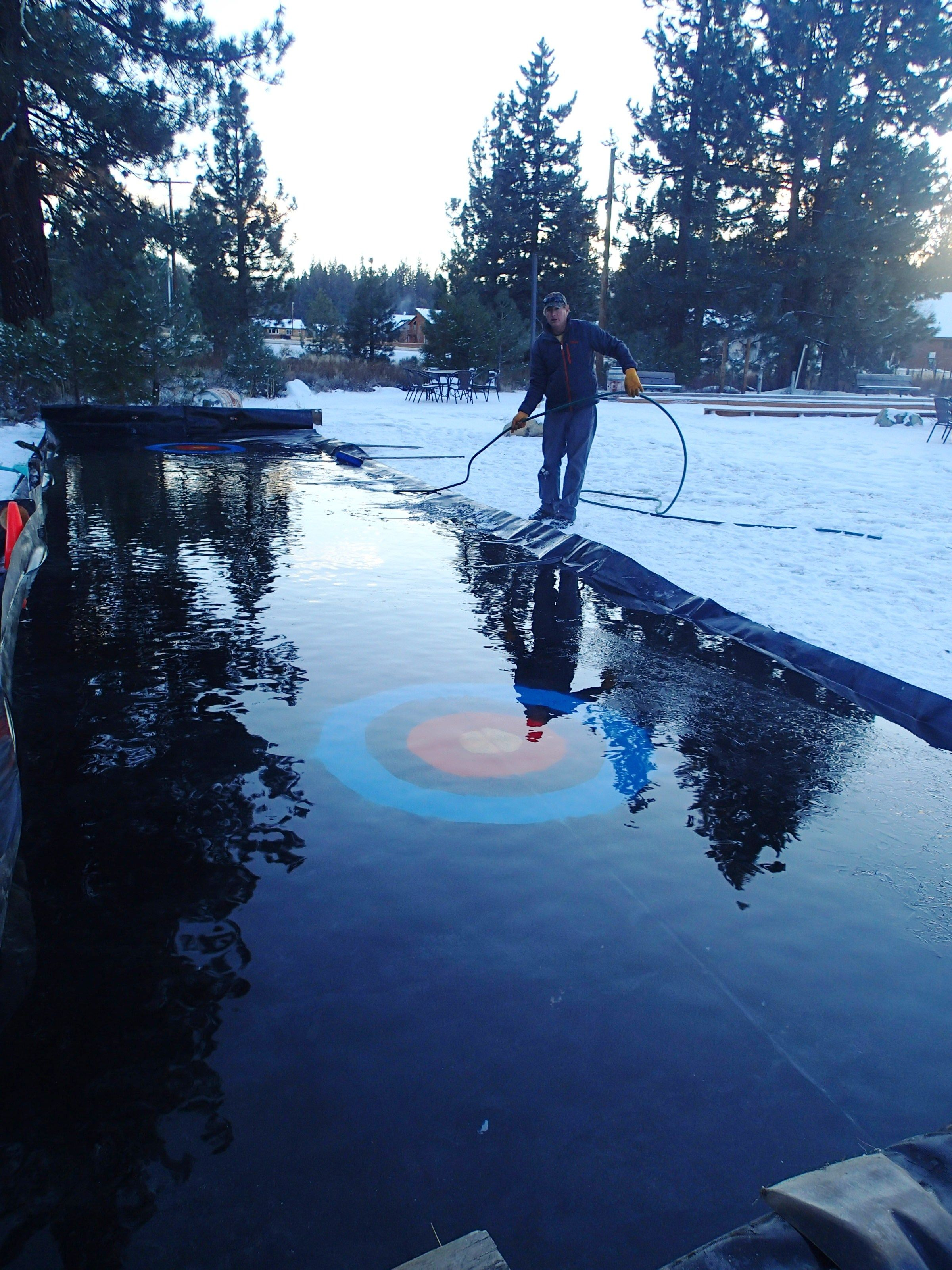 Russ Jones making a curling court in the backyard of the tasting room!