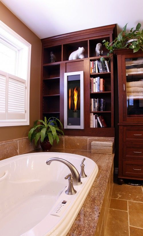 Love this library feel with 'fireplace'.  Books in the bathroom? Yes! Books are a great accessory in ANY room!