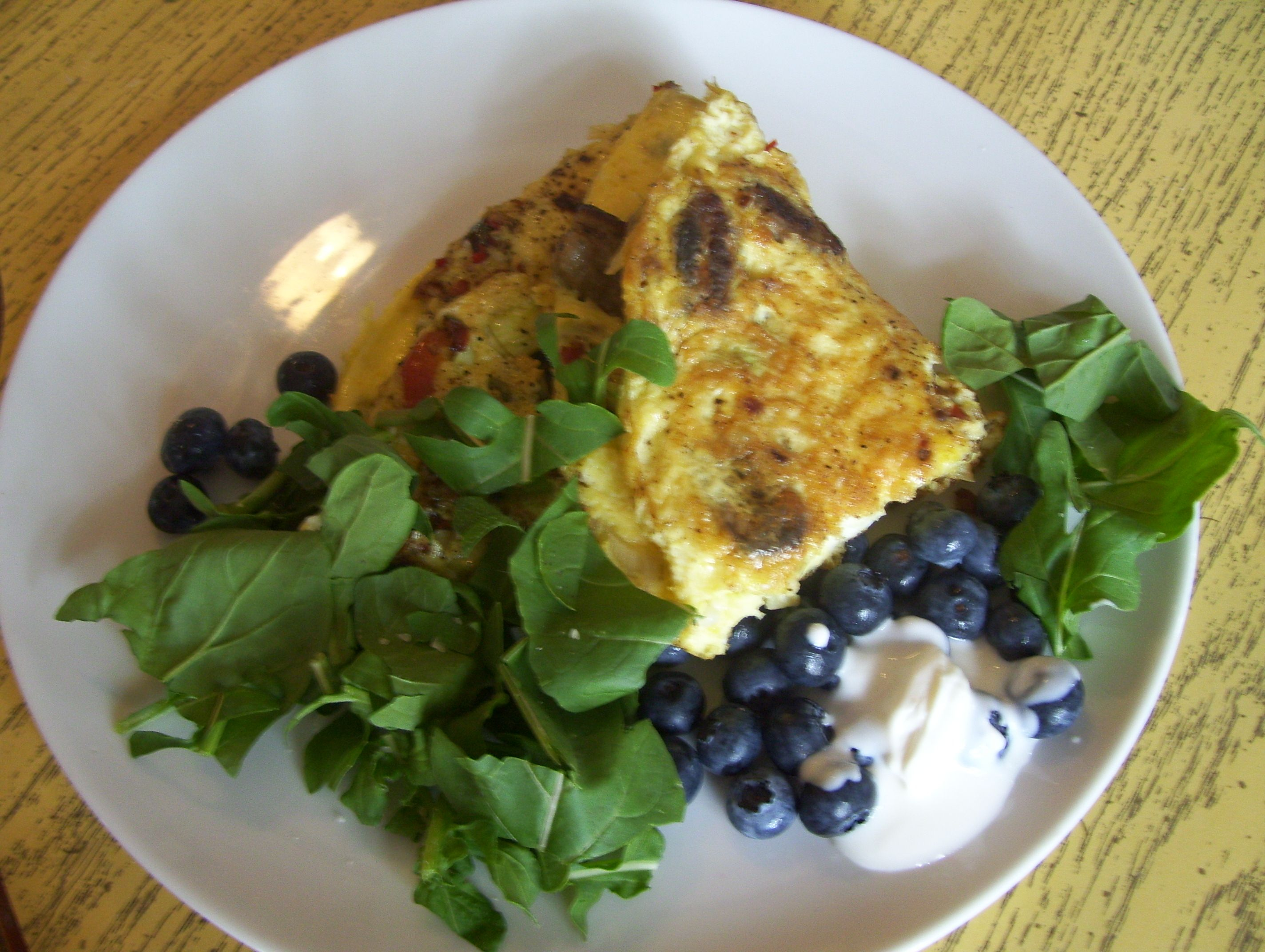 Folded frittata with hot peppers, sweet peppers, baby okra, baby squash, garlic, and parmesan... with fresh arugula, blueberries and home made yogurt!