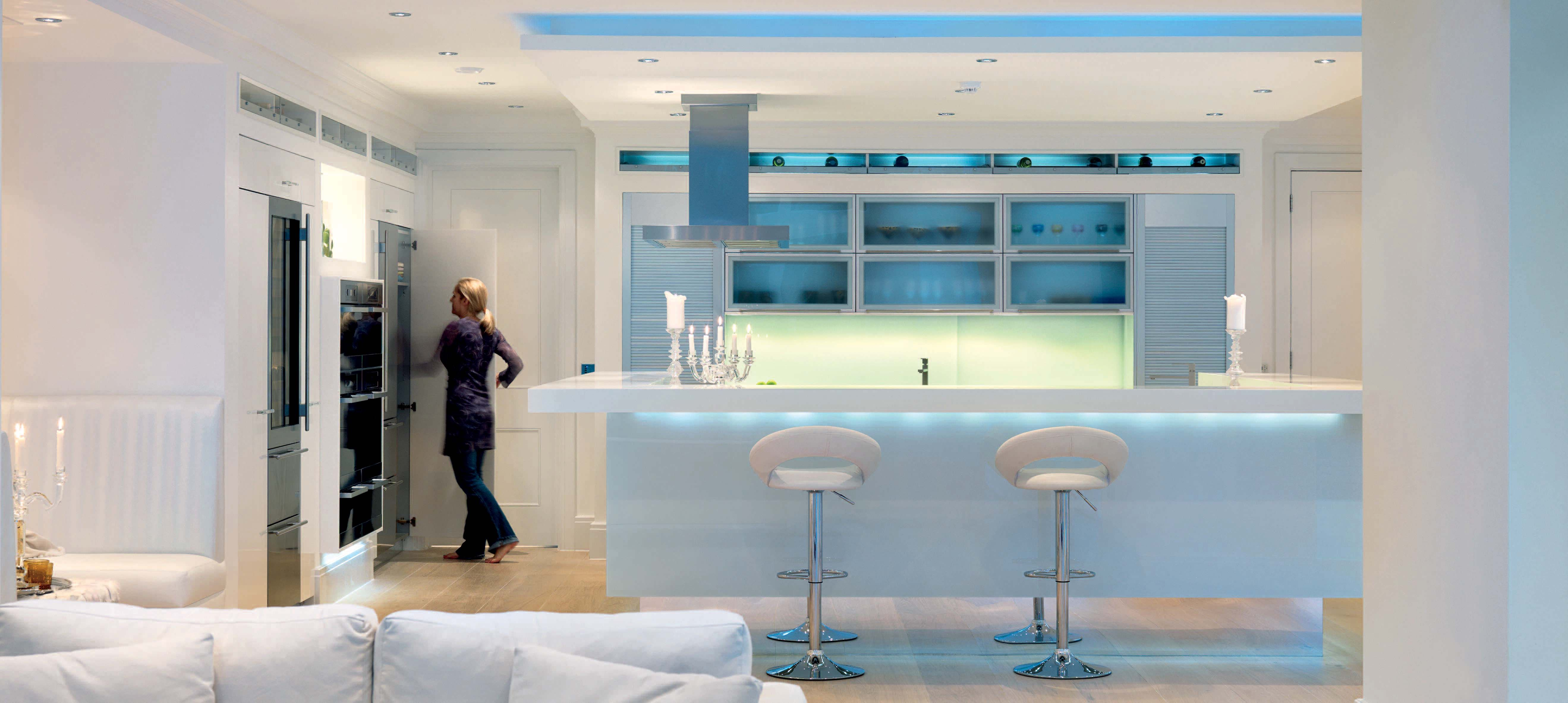 Clean white eating area in the kitchen with clever lighting to ...