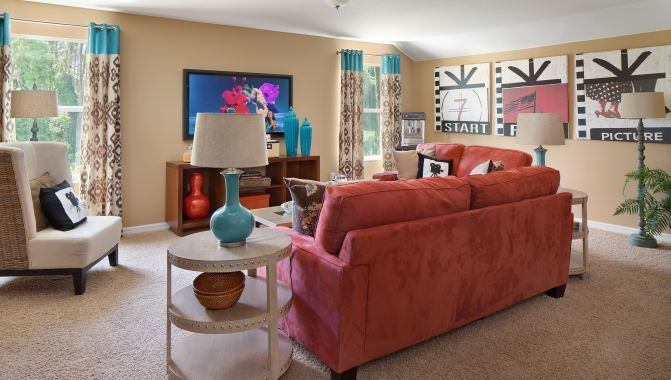 Coral Couch and robin's egg blue accents | New Homes in Ruskin | Belmont community | St Augustine II 2nd Floor Bonus Room