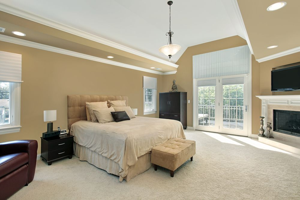 This Expansive Bedroom Features A Cushioned Head Board And Matching Sand Colored Ottoman Hearth With
