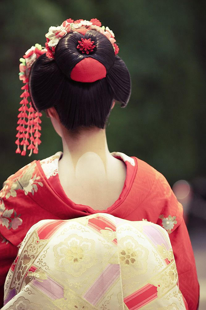 Maiko's back view. Please note the carefully revealed portion of the Maiko's real neck skin.  Japanese men find the nape of a woman's neck very attractive, a bit like a woman's breast cleavage in western culture.