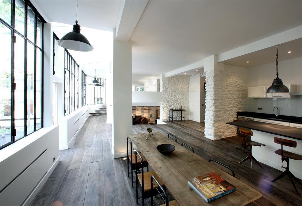 Visite privée dun loft en plein montmartre rénové avec un parquet à lames larges des meubles laqués blancs sur mesure une immense verrière ourant sur la