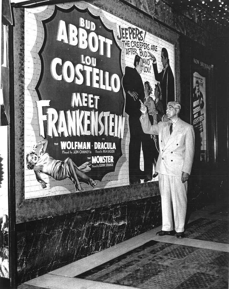 """Boris Karloff stands in front of a movie poster for """"Abbott and Costello Meet Frankenstein""""."""