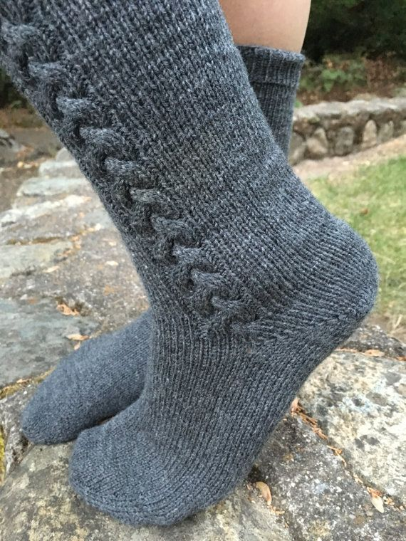 These beautiful knitted socks are worked from the toe up, making them easy to try on as you go.The cabled braid worked on the outside of each sock adds a touch of elegance, while the ribbing at the top stretches to create a snug-fitting band. These are a wonderful first-time toe-up sock project, sure to please and fun to make!  Materials: 1 skein JaggerSpun Sock Yarn, shown in color Steel Needles: Set of 4 in U.S. size 1 double pointed needles, or circulars. Notions: Stitch marker, cable…