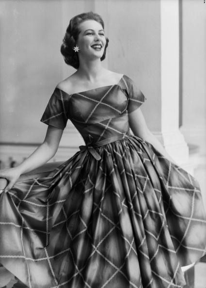 Model sporting a full skirted checked dress with off the shoulder short sleeves, October 1955