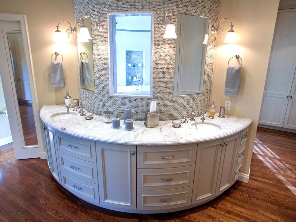 A half-moon shaped vanity displays a multi-colored neutral tile backsplash, marble countertops and several cream-colored drawers and cabinets.