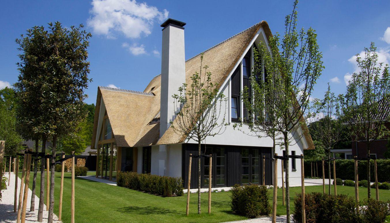 Modern reitgedekt met oversteek en eikenhouten accent for Architecten moderne stijl