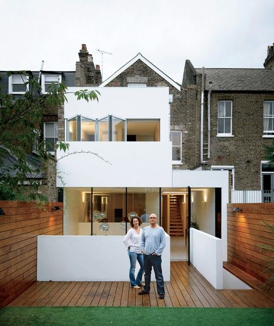 White acrylic stucco addition on brick house with wood deck. Dwell.