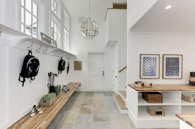 White Cottage Mudroom Features A Long Floating Wood Bench Fixed Against A White Shiplap Trim And