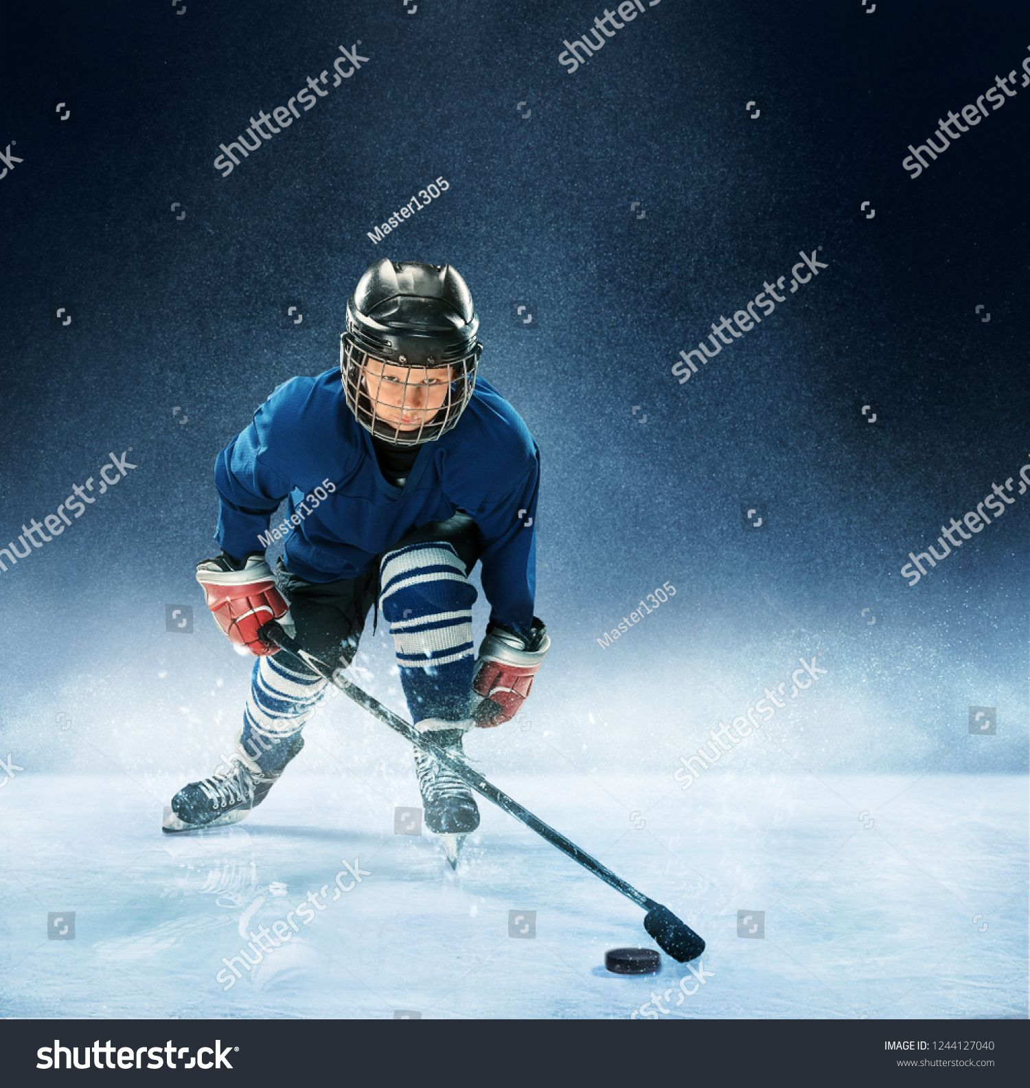 Little boy playing ice hockey at arena A hockey player in uniform with equipment over a blue background The athlete child sport action concept