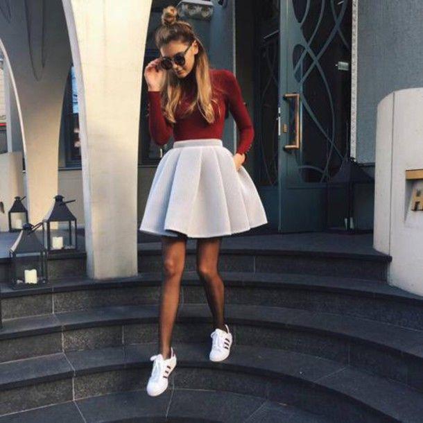 Burgundy long sleeved top. White skirt. Adidas shoe.