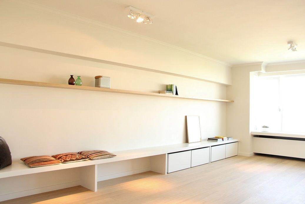 Photo of leefruimte met bank zwevende legborden en afwerking van de radiator