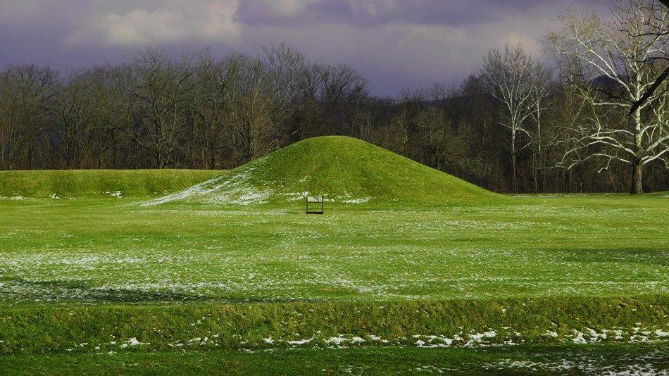 A large grasscovered mound under a dark grey sky