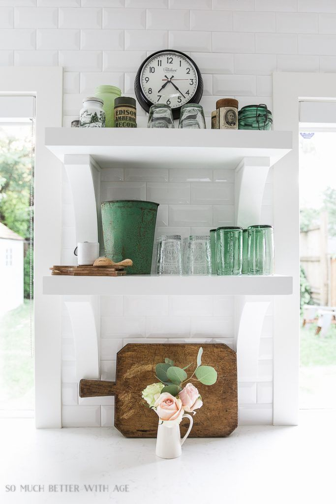 French vintage style: antique green glass and simple flower arrangements. Get more tips on how to get the look! #frenchvintage #openshelving