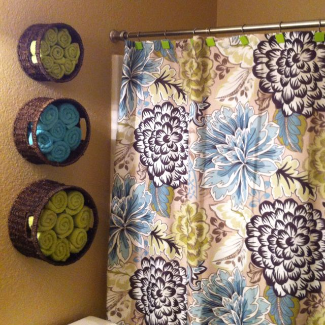 rolled up bathroom towels stored in baskets on wall -- decorative and space efficient!