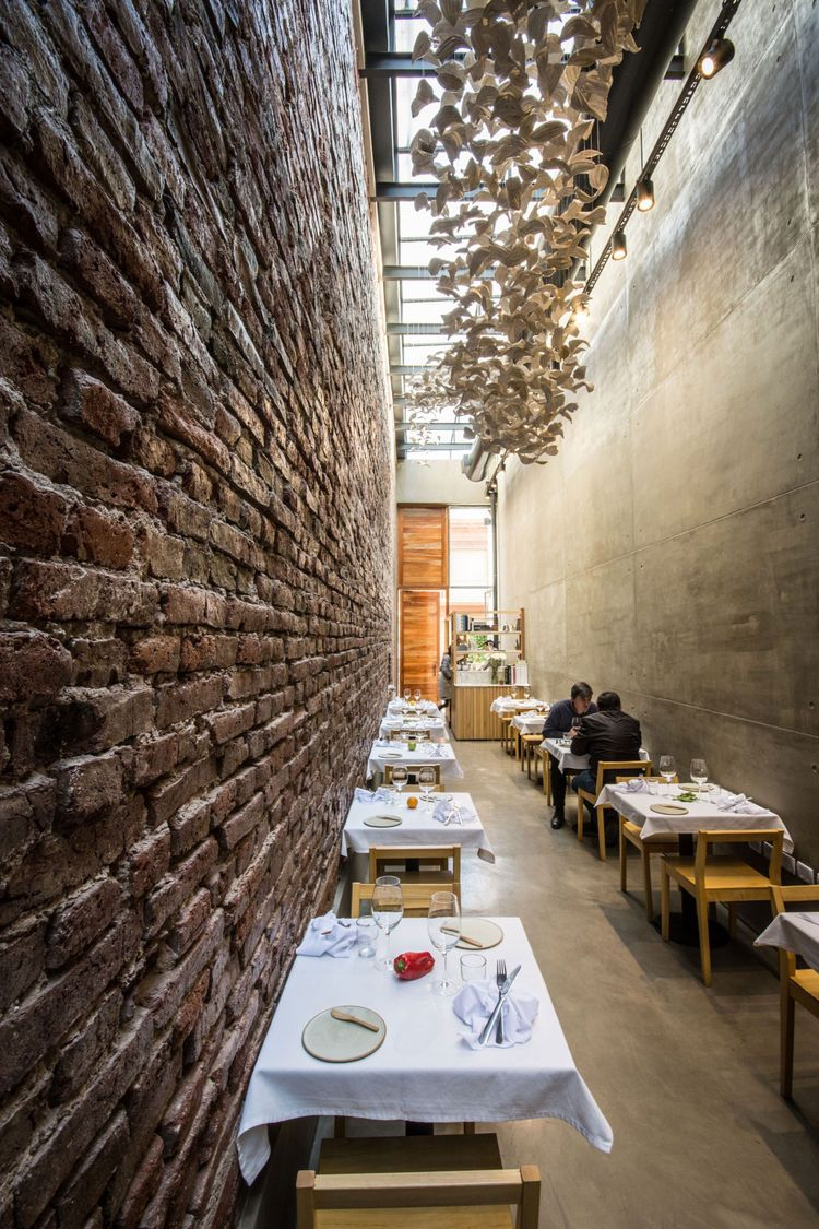 modern restaurant , 8 feet wide, with brick walls and concrete